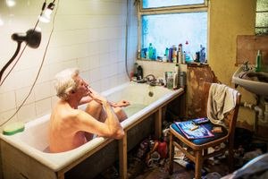 George smokes a cigarette while taking a bath. As one of the few accessible spaces in his four bedroom house, George often uses his bathtub to read, have a coffee, wash the dishes and do his laundry.   © Corinna Kern
