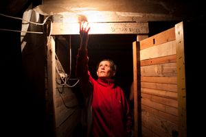 An Israeli homeless woman fixes a light in her make-shift house, in a park in South Tel Aviv, Israel, 2011.