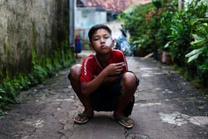 Rian, who smokes occasionally, smokes a cigarette in east Jakarta, Indonesia. © Michelle Siu