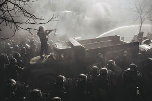 Riot policeman shot from pump gun standing on a burned truck during the confrontation on Shelkovichna street when protestors stormed Verhovna Rada (Ukrainian parliament). Kiev, Feb. 18, 2014