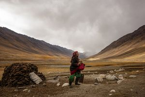 A wakhi nomad woman is bringing cow dung into her stone shelter in one of the valleys of the little Pamir.