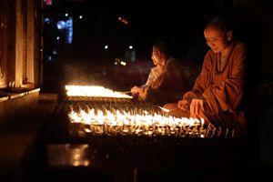 A nun lights butter lamps around Boudhanath Stupa