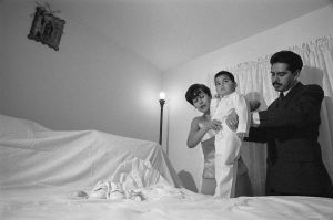 Eduardo Reyes being dressed for his baptism by his parents.