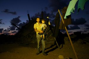 Mohamed Abu Samhain, 26, and his 2 year old son Rain Mohammed Samhain pose in front their destroyed home in Khan Yunis by Israeli airstrike and bulldozers during the summer's 50-day war between Israel and Hamas. They have to still live at the site, since there is no place else for them to move, or too expensive for the rent after the war.