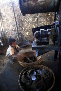 © 2014, Stephen Shames — Bangladesh. Small child works in metal shop.