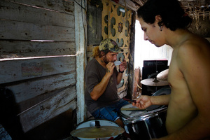 Karlos repairing his drums, and Jimmy, from Kaoz band in St. Clara