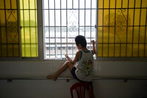 A boy born with protruding eyes and deformed limbs looks out the window. Children at Peace Village merely leave the ward.