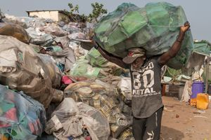 A worker carries a bunch of plastic that will be sold to a company in the region.