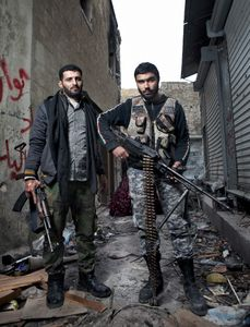 Two FSA rebels hold their weapons for a portrait near a front line checkpoint in the old city district of Aleppo on February 9, 2013. © Nish Nalbandian