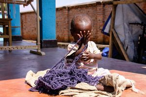 Toddler Plays Pee-a-Boo with Hand-spun Yarn, Musanze Rwanda Africa