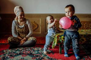 A Uighur woman observe her children playing at her apartment house in Kashgar, Xinjiang Uighur Autonomous Region, China.