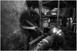 A child labor operating a lathe machine.