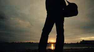 A man standing in front of the sunset