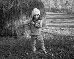 Cocon, Sirbi, 2000. Petruc will soon begin helping his father wrangling horses in summer and carrying water from the frozen river in winter. As he grows, his hands will become large and callused from hard work. Yet his mother will never let him go outside without covering his head. © Kathleen Laraia McLaughlin.