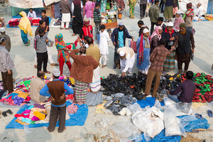 Many people seat on street near the Istema camp to sell products