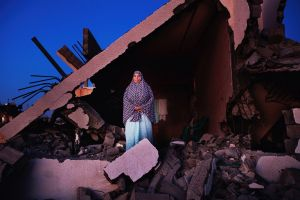 Sobheya Hamid Abu Mutlag, 59, poses at her home in Khan Yunis destroyed by Israeli artillery during the summer's 50-day war between Israel and Hamas. Despite the serious damage, she cannot leave, since there is no place else for her to move, or too expensive for the rent after the war.