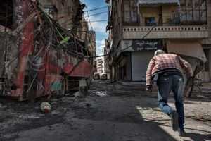 A YPG fighter sprints across an intersection to avoid Syrian government army sniper fire in the Ashrafieh district in Aleppo on April 20, 2013. © Nish Nalbandian