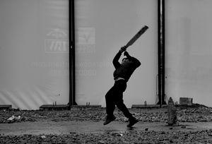 una partita a cricket, con una racchetta improvvisata