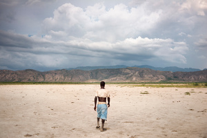 A man walking to his village through Savanne Dèsolèe, considered to be the largest desert area of the country. In the background, one sees deforested mountains.