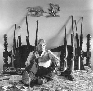Test Site Worker Rex Tomlinson with his gun collection ... in better days.  Las Vegas, Nevada, 1988