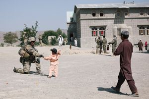 """A member of the Provincial Reconstruction Team's Security Force gives a local child a """"low five"""" while the PRT assesses a primary school for possible repairs."""