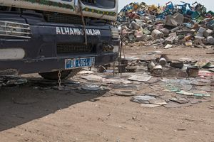 A truck drives over cans that workers have spread on the street so that the metal gets pressed together.
