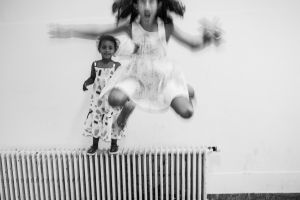 an Eritrean girl and a Syrian girl play in the hallway of the asylum centre  © Alison McCauley