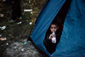 A child peeks through the tent entrance in the refugee camp at Spielfeld, Austria