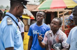 A Sierra Leone Police Officer is approached by a man by a bust market place.