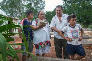 Doña Celestina Pat, Don Antonio Moo Argona and two of their grandchildren visit the grave of Antonio's mother.