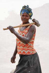 L. Stella. Works in quarry breaking stones to make gravel.  Earns 1,000 shillings ($0.32) per Jerrycan of gravel. Makes 10 -15 Jerrycans of gravel per day.
