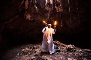 A vodou priest summons spirit of Ezrili during a cave ritual. Once possessed, the lwa takes over and uses the servant to drink, dance and offer advice. Ezrili Danto is one of the most famous and universally honored Lwa in Haitian Vodou. Danto is depicted with an image of the Blessed Virgin Mary.