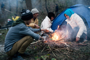 Family of migrants next to their campfire, preparing for the tough night in refugee camp at Spielfeld, Austria