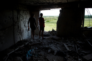 The owners of the ruined apartment look in the direction from which tank shell flew; Donetsk airport controlled by pro-Russian militants can be seen from the windows. Avdeevka near Donetsk. July 18, 2015.