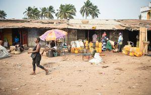 A woman walks down a street in Sierra Leone. Shops can be seen in the background.