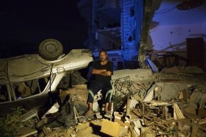 55 year old taxi driver Mohamed Abu Jama'a poses next to his  destroyed mercedes taxi and home in Khan Yunis due to Israeli airstrike and bulldozers during the summer's 50-day war between Israel and Hamas. He has to still live at the site, since there is no place else for him to move, or too expensive for the rent after the war.