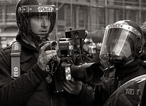 Police photographer at Mayday protest, London, 2002.
