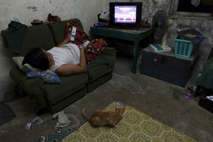 Working from home mom watch TV at her rest in Yuzana Garden City, Yangon, Myanmar.