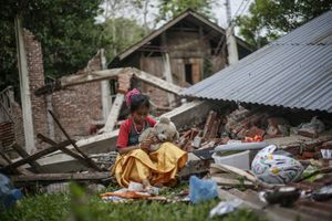 Rizka Martunis, 9 years old, hugging her teddy bear as she sitting outside her destroyed home due to 6.5 magnitude earthquake in Pidie Jaya, Aceh province, on December 10, 2016.