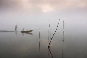 Fisher returning home through the dawn mist at Borghetto, Lake Trasimeno, Umbria, Italy
