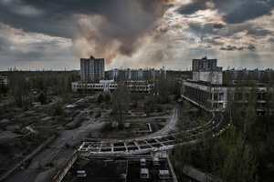 the forest burns behind the ghost city of Pripyat.One of the greatest dangers existing in the exclusion zone are fires. Fire burns trees raising radioactive ash that is spread in the air, causing a new nuclear fallout.