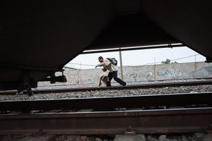 A migrant picks up a piece of cardboard that will use later to protect himself from the cold while travels at top of train, in State of Mexico, Mexico, May 20, 2008.