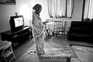Muslin woman prepares herself to pray in her apartment. Her family has moved from Sudan to United States one year ago.Queens, New York, NY, United States.