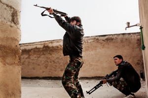 A Free Syrian Army fighter shooting against the position of an Al-Assad sniper; another one preparing to shoot in a while with an heavy machinegun.