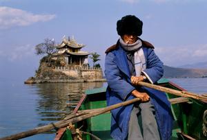 Man rowing to temple, Yunnan, China, 1992.