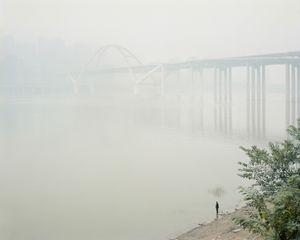 Pêcheur dans la brume au pont Cayiuanba Changjiang. District de Yuzhong, Chongqing. Chine, Décembre 2017.