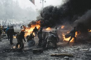 A protester carries a burning car ramp closer to the riot police cordon in the center of Kiev on Jan. 22, 2014.