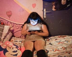 Maddelena, 11 years old, is playing with the little tab that she got for her birthday, in the bedroom that she shares with her sister Ilona, 12 years old and her mother Françoise.