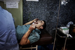 A wounded man cries out in pain as a doctor treating him in Dar Al-Shifaa hospital.