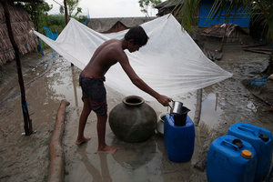 A boy collects rainwater by using a plastic sheet, as they have no tin roof. Rainwater is the main source of drinking water of the Shyamnagar villagers. Satkhira, Bangladesh